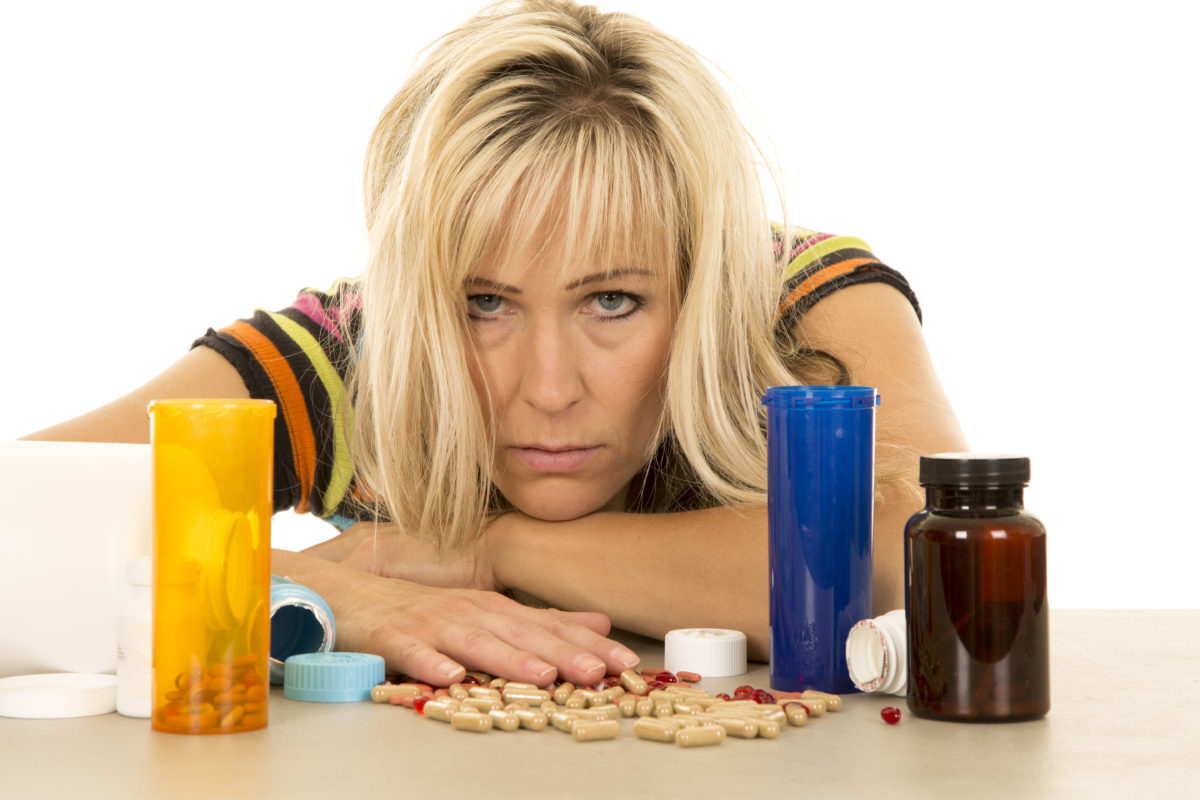 woman with medication, supplements, too many, overdose, Lyme, chronic illness, naturopath, functional, medicine, supplements
